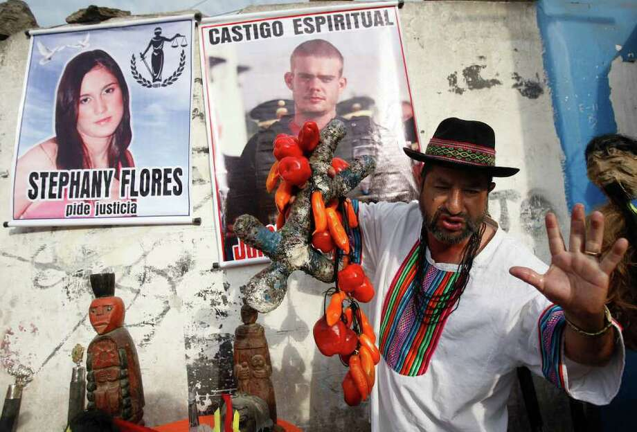 "A shaman performs a ritual for the spiritual punishment of Joran van der Sloot, in poster top center, and for justice for Stephany Flores, in poster at left, before Van der Sloot's trial outside the prison where the trial will be held in Lima, Peru, Friday Jan. 6, 2012.  Van der Sloot goes on trial Friday for the murder of a young Peruvian woman, nearly seven years after he became the prime suspect in the unsolved disappearance of an American teenager on holiday in Aruba.  Van der Sloot, 24, is charged with killing 21-year-old Stephany Flores in his Lima hotel room on May 30, 2010, after the two left a casino together in the day's wee hours.  The poster of Flores reads in Spanish ""Stephany Flores asks for justice"" and the poster of Van der Sloot reads ""Spiritual punishment."" (AP Photo/Karel Navarro) Photo: Karel Navarro, Associated Press / AP"