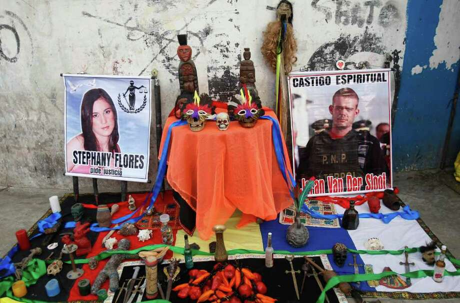 "Posters of Joran van der Sloot, right, and Stepahny Flores, left, sit among items from a shaman ritual outside San Pedro prison where Van der Sloot's trial will start in the area of Lurigancho in Lima, Peru, Friday Jan. 6, 2012.  Van der Sloot goes on trial Friday for the murder of a young Peruvian woman, nearly seven years after he became the prime suspect in the unsolved disappearance of an American teenager on holiday in Aruba.  Van der Sloot, 24, is charged with killing 21-year-old Flores in his Lima hotel room on May 30, 2010, after the two left a casino together in the day's wee hours. The poster of Flores reads in Spanish ""Stephany Flores asks for justice"" and the poster of Van der Sloot reads ""Spiritual punishment."" (AP Photo/Karel Navarro) Photo: Karel Navarro, Associated Press / AP"