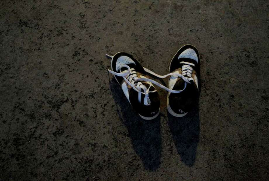 A pair of shoes belonging to a homeless man is seen in a parking lot in Santa Ana , Calif., Thursday. Homeless people in Orange County are put on alert by police and advocates concerned that they're the target of a serial killer who has already slain three homeless men. Police said an attacker has stabbed three homeless people to death in north Orange County. Photo: AP