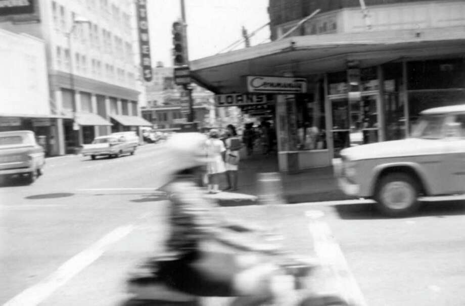 Houston Street, looking east from Flores Street. We'd seen the young woman on the motorbike — a rather unusual sight in the mid-'60s — several times before taking this picture. In much sharper focus than the biker is the Stowers Furniture building to the left. Photo: Kolarik / To be published ONLY on the iPad edition.
