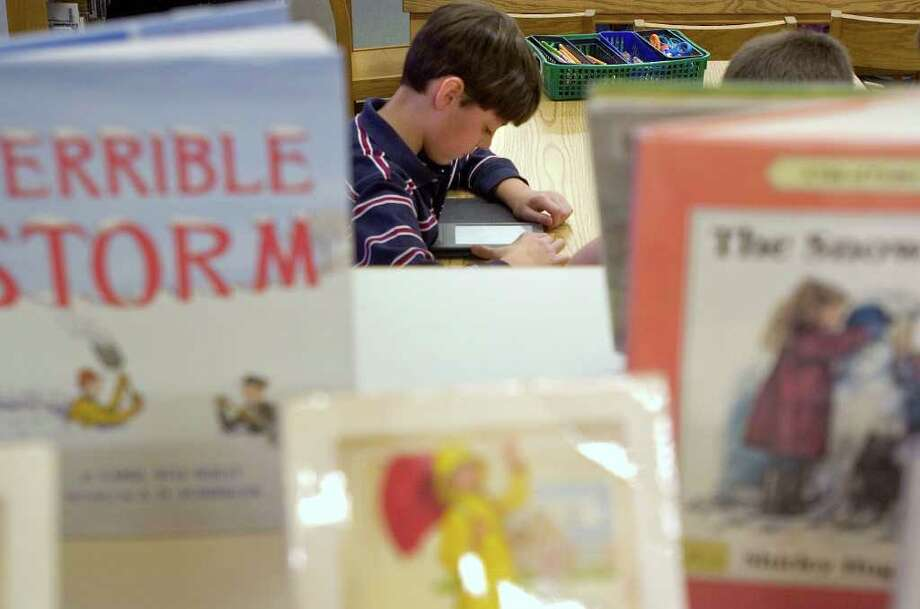 Fourth-grader Dylan Nascimento, 9, reads an Amazon Kindle instead of a printed book in the library at Sandy Hook Elementary School in Newtown on Friday, Jan. 6, 2012. Photo: Jason Rearick / The News-Times