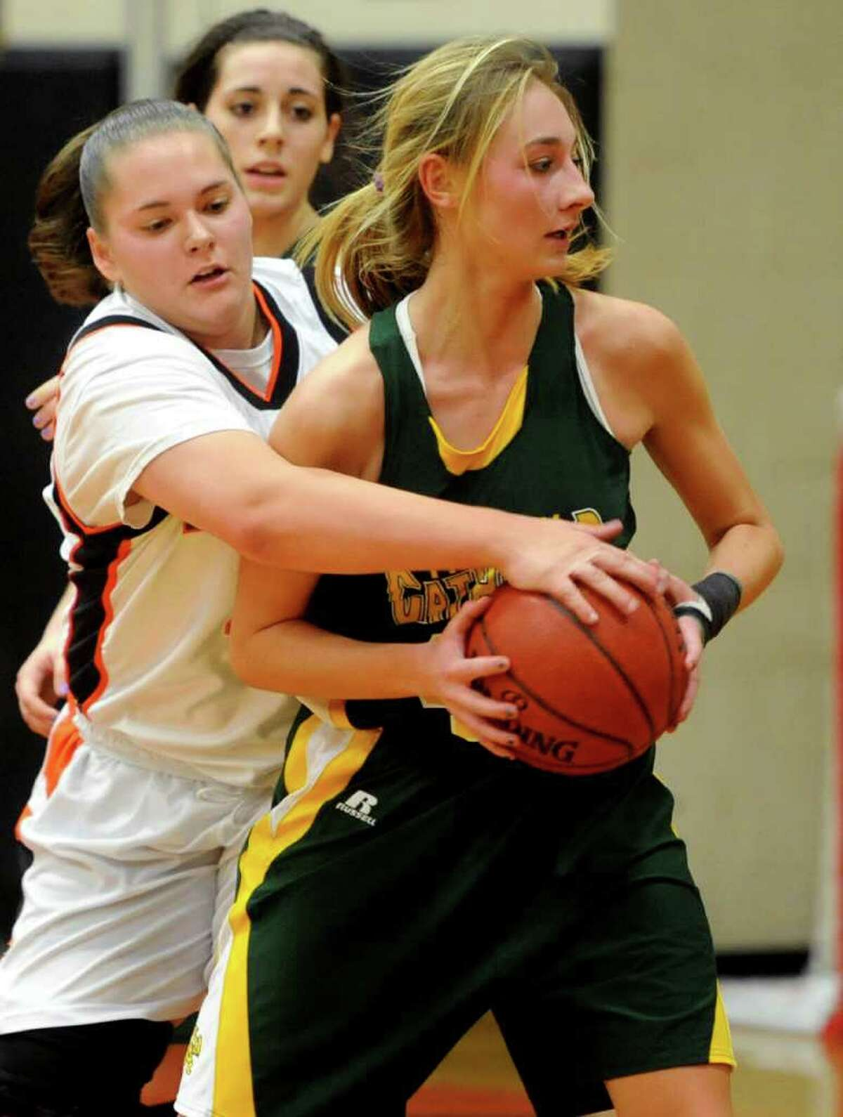 Trinity Catholic's Mackenzie Griffin holds on to the ball as Stamford's Kelsey Santagata attempts to knock it away during the girls basketball game at Stamford High School on Friday, January 6, 2012.