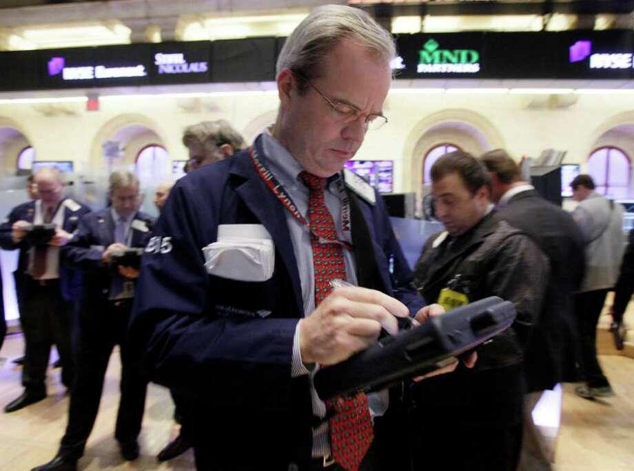 FILE - In this Dec. 13, 2011 file photo, trader David O'Day, center, works on the floor of the New York Stock Exchange. European stocks rose on Friday as investors set aside concerns about the euro's debt crisis to focus on the impending release of monthly U.S. jobs data, which many hope will confirm a mild recovery in the world's largest economy. (AP Photo/Richard Drew, File) Photo: Richard Drew