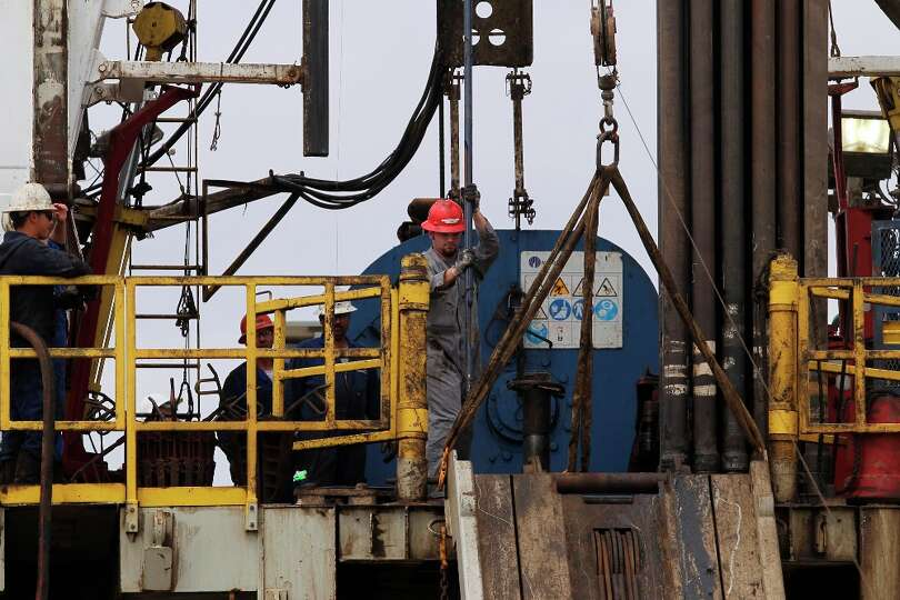 Oil workers are shown on a rig over the Eagle Ford Shale formation near Tilden last March. Marube