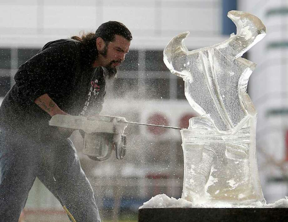 The Reverend Butter, aka Rolando De La Garza, carves the Houston Texans mascot, Toro, into a 300-pound piece of ice at Discovery Green, Friday, Jan. 6, 2012, in Houston. He was warming up for the Stella Artois Dirty Dozen: 4th Annual Ice Sculpting Competition, Saturday, January 7, 2011. Photo: Karen Warren, Houston Chronicle / © 2012  Houston Chronicle