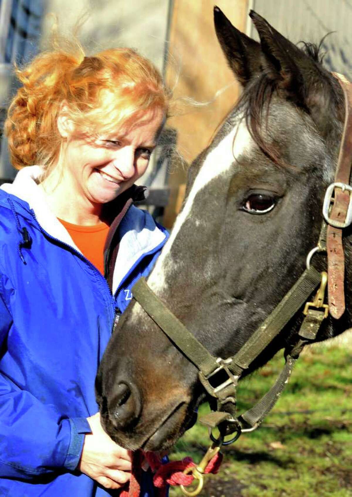 Annette Sullivan stands with Burma's Lady, the horse she rescued from slaughter, at her Zoar Ridge Stables in Newtown Thursday, Dec. 8, 2011.