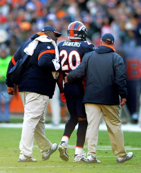 Broncos safety Brian Dawkins is helped off the field after pinching a nerve in his neck Dec. 11 against Chicago. Photo: AP