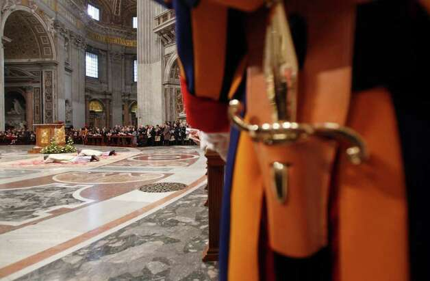 A Swiss guard stands, right, as newly elected US bishop Charles John Brown, left, and newly elected bishop Marek Solczynski from Poland lay on the ground during their ordaining ceremony led by Pope Benedict XVI in St. Peter's Basilica at the Vatican, Friday, Jan.  6, 2012. (AP Photo/Pier Paolo Cito) Photo: Pier Paolo Cito / AP