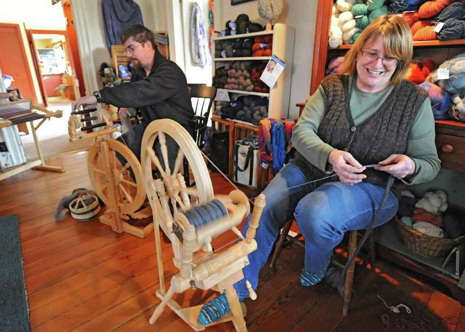 Carole Foster spins wool on her spinning wheel in her home which is also The Knit Shop at Foster Sheep Farm Friday, Jan 6, 2012 in Northumberland, N.Y.  Her son Greg also spins wool next to her. (Lori Van Buren / Times Union) Photo: Lori Van Buren