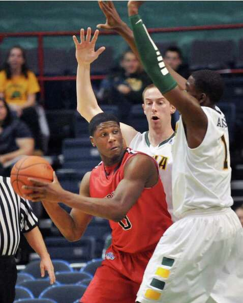Fairfield's #15 Maurice Barrow, left, gets boxed in by Siena's #31 Owen Wignot and #1 OD Anosike dur