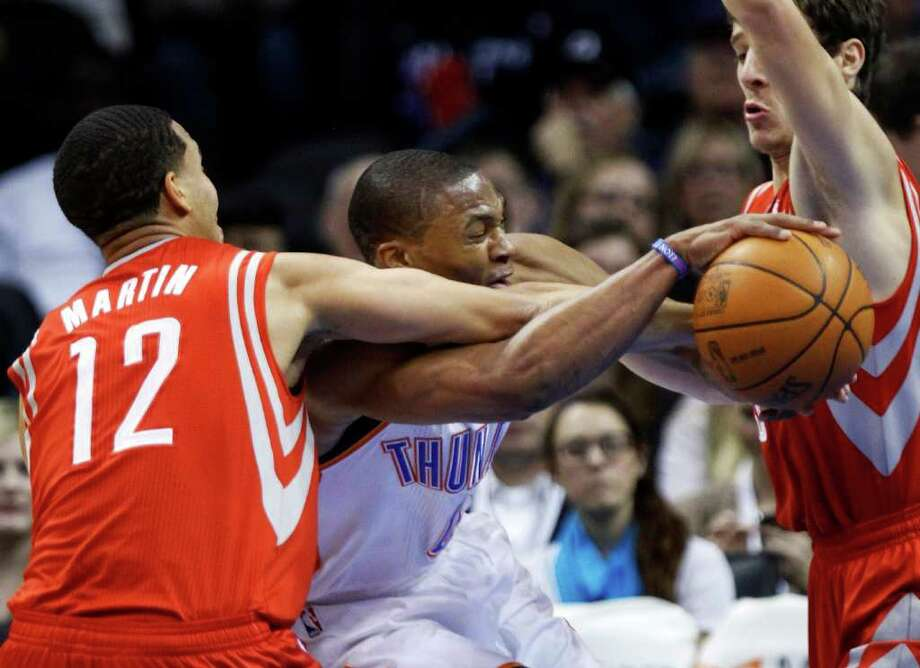 Oklahoma City Thunder guard Russell Westbrook, center, is fouled by Houston Rockets guard Kevin Martin (12) in the first quarter of an NBA basketball game in Oklahoma City, Friday, Jan. 6, 2012. Houston guard Goran Dragic, of Slovenia, right, moves in. Oklahoma City won 109-94. (AP Photo/Sue Ogrocki) Photo: Sue Ogrocki, Associated Press / AP