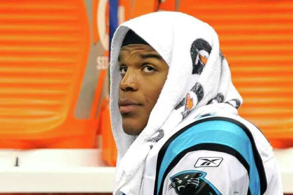 Carolina Panthers quarterback Cam Newton sits on the bench late in the fourth quarter of an NFL football game against the New Orleans Saints in New Orleans, Sunday, Jan. 1, 2012. The Saints won 45-17. (AP Photo/Bill Feig)
