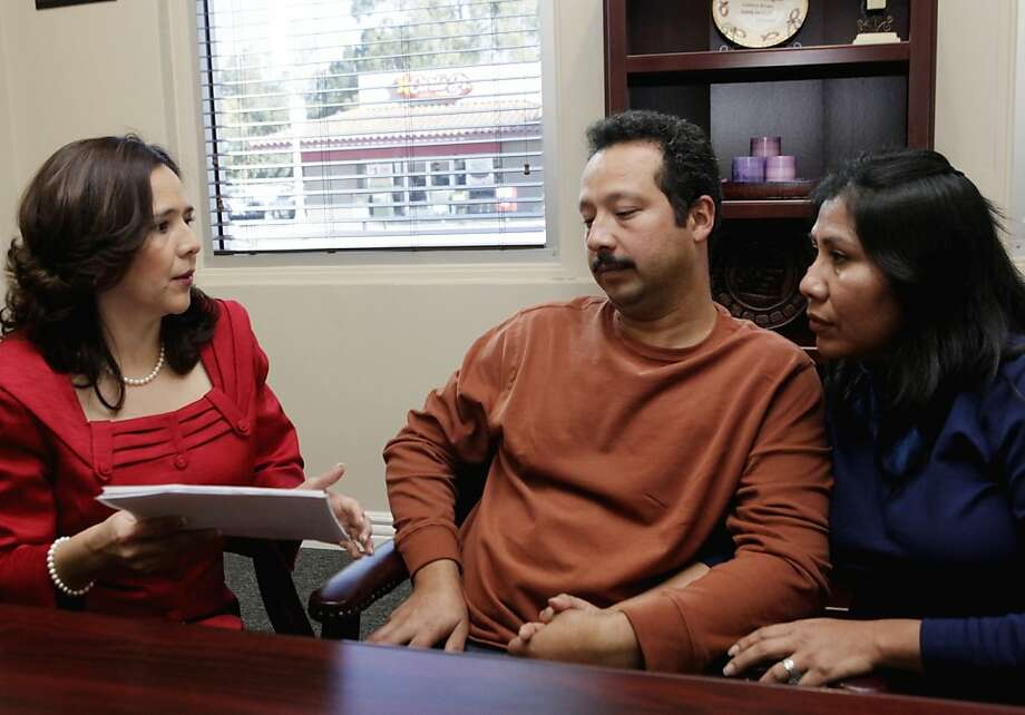 Attorney Jessica Dominguez, left  speaks with Jose Luis Barajas and his wife, Laura Barajas at Dominguez' office in Los Angeles Friday, Jan 6, 2012. The Obama administration proposed a rule change Friday Jan. 6, 2012 to reduce the time that illegal immigrant spouses and children are separated from their American relatives while they try to gain legal status in the United States. The couple are getting advice from Dominguez for Laura, who is in the country illegally, and her proposed trip to Mexico to get her legal papers. Her husband Jose has legal papers.  (AP Photo/Nick Ut) Photo: Nick Ut, Associated Press