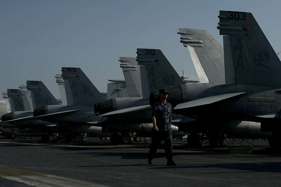 A US Navy serviceman walks past F/A-18 Hornet warplanes on the flight deck of the USS Carl Vinson, a US nuclear powered aircraft carrier anchored in Hong Kong on December 27, 2011.  The USS Carl Vinson, which was commissioned in 1982, is in Hong Kong for a three day visit.  AFP PHOTO / AARON TAM (Photo credit should read aaron tam/AFP/Getty Images) Photo: Aaron Tam, Getty