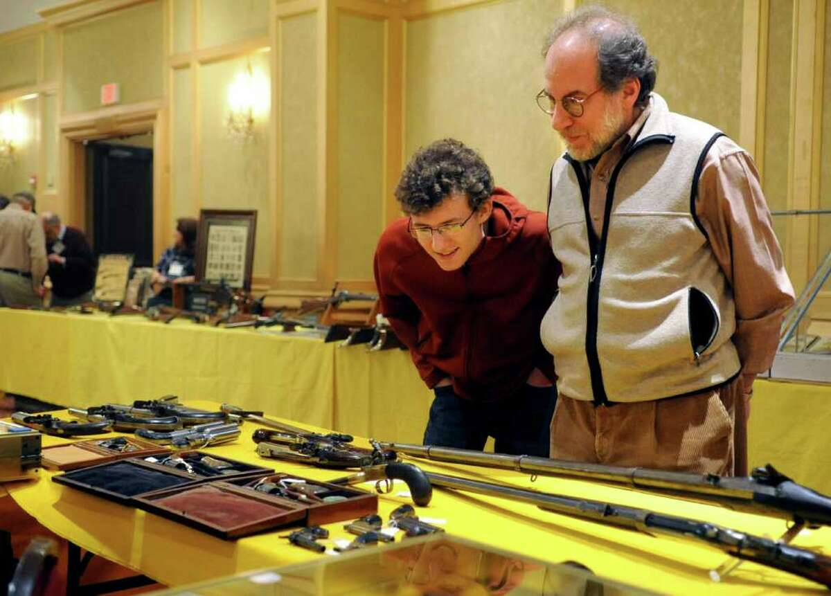 Charles Rothbart and his father, Carl, of New Canaan look at items for sale at the seventh annual East Coast Fine Arms Show at the Plaza Hotel in Stamford on Saturday, January 7, 2012.