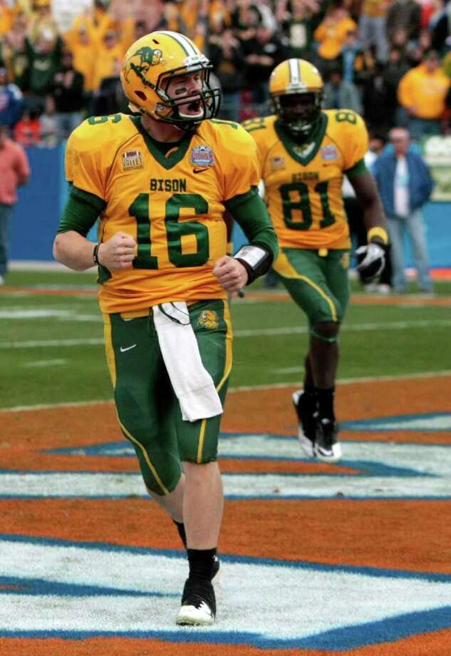 North Dakota State University quarterback Brock Jensen (16) celebrates a rushing touchdown as North Dakota State University wideout Warren Holloway (81) joins in.  During the fourth quarter of  Sam Houston State University  and North Dakota State University match up in the 2012 Division I Football Championship at Pizza Hut Park in Frisco, Texas January 7, 2011. North Dakota State University beat Sam Houston State University 17-6. Photo: Billy Smith II, Chronicle / © 2012 Houston Chronicle