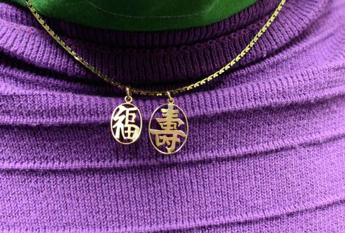 Susan Cohen, of Greenwich, proudly displays the Chinese characters on her necklace, one represents good fortune, the other longevity, in the lobby of her home in Greenwich on Friday, Jan. 6, 2012.