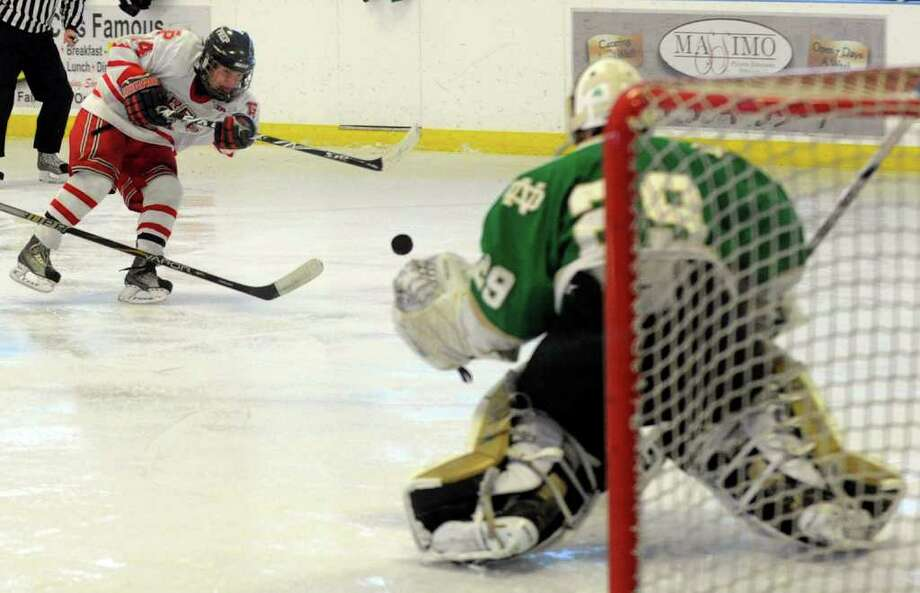 Fairfield Prep's #24 Conor Peterson, left, hits a slap shot as Notre Dame of West Haven goalie Luciano Amatruda prepares to stop it, during boys hockey action in Bridgeport, Conn. on Saturday January 7, 2012. Photo: Christian Abraham / Connecticut Post