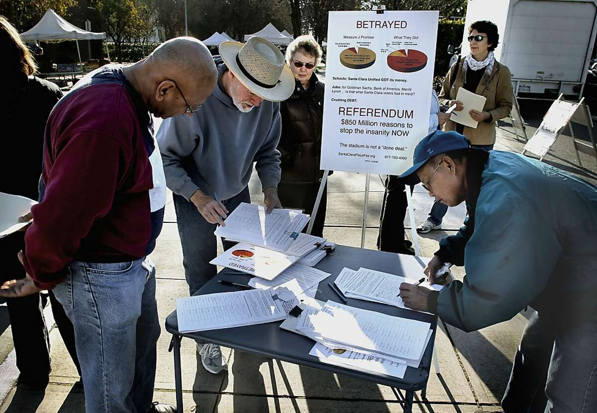 """Volunteer, Kay Khandpur, (left) helps with signatures, as members of Santa Clara Plays Fair, hold a """"Save Santa Clara Saturday"""" at the Farmer's Market in Santa Clara, Ca., on Saturday Jan. 7, 2012, to gather signatures on a petition to stop the 49ers stadium project. They want the Santa Clara City Council to reconsider it's recent decision to encumber a city agency with $850 million in loans to construct a stadium for the San Francisco 49ers."""