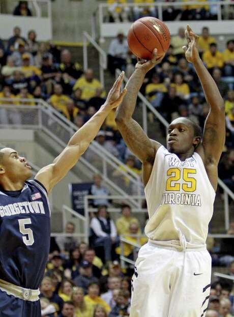 West Virginia's Darryl Bryant (25) shoots over Georgetown's Markel Starks (5) during the second half of an NCAA college basketball game in Morgantown, W.Va., on Saturday, Jan. 7, 2012. West Virginia won 74-62. Photo: AP