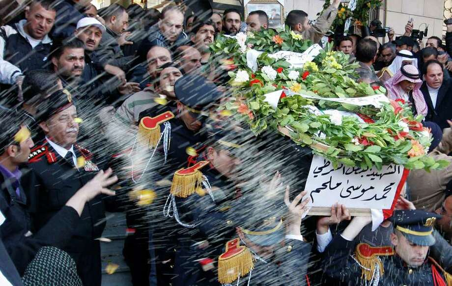 """Syrian mourners throw rice in traditional fashion as police honor guards carry the coffin of one of 11 Syrian officers who were killed in an explosion in the Midan neighborhood on Friday, during a mass funeral procession at Al-Hassan mosque, in Damascus, Syria, on Saturday Jan. 7, 2012.  Thousands of regime backers massed at a mosque in the Syrian capital Saturday for funeral prayers for policemen killed in a Damascus bombing, as the government vowed to respond with an """"iron fist"""" to security threats. (AP Photo/Muzaffar Salman) Photo: Muzaffar Salman / AP"""