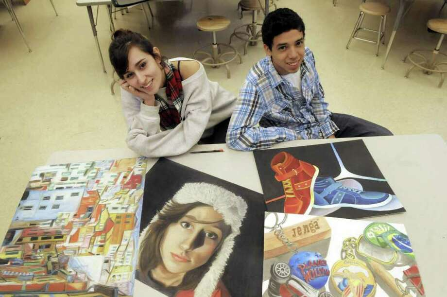 Guilderland High School seniors and art students, Madi Taylor, left, and Albert Cartagenes poses with some of their artwork  in one of the art rooms at the high school on Tuesday, Dec. 20, 2011 in Guilderland, NY.  The two pieces on the left are Taylor's work, which includes a self-portrait and the two pieces on the right are Cartagenes' work.  (Paul Buckowski / Times Union) Photo: Paul Buckowski / 00015827A