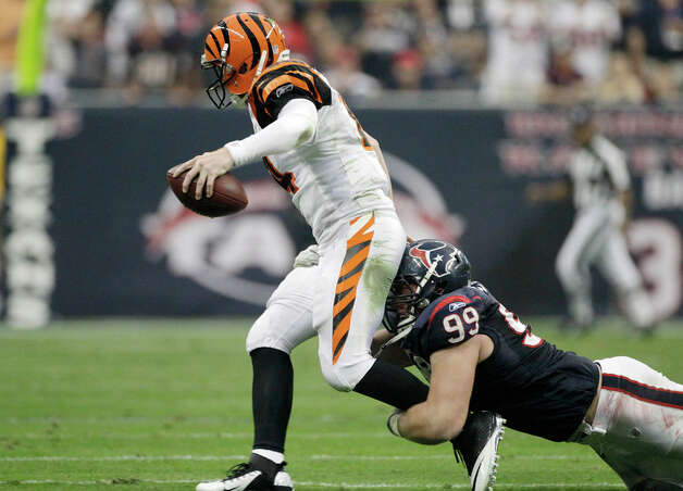 Houston Texans defensive end J.J. Watt (99) grabs Cincinnati Bengals quarterback Andy Dalton (14) for a sack during the second quarter of an NFL wild card playoff football game Saturday, Jan. 7, 2012, in Houston. Photo: Tony Gutierrez, Tony Gutierrez, Associated Press / AP