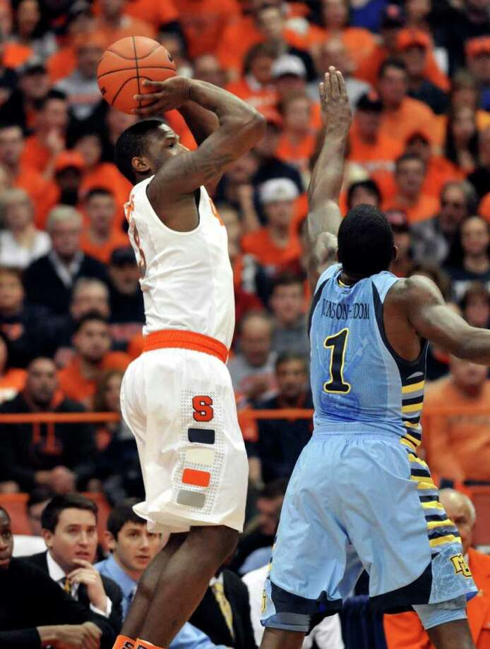 Syracuse's Dion Waiters, left, shoots over Marquette's Darius Johnson-Odom during the first half of an NCAA college basketball game in Syracuse, N.Y., Saturday, Jan. 7, 2012. (AP Photo/Kevin Rivoli) Photo: Kevin Rivoli