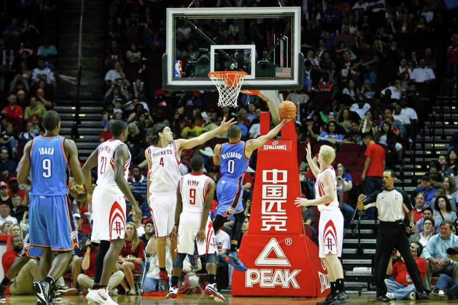 Oklahoma City Thunder point guard Russell Westbrook (0) puts up a shot over Houston Rockets power forward Luis Scola (4) during the Houston Rockets vs. Oklahoma City Thunder NBA basketball game at the Toyota Center, Saturday, Jan. 7, 2012, in Houston. Photo: Michael Paulsen, Houston Chronicle / © 2011 Houston Chronicle