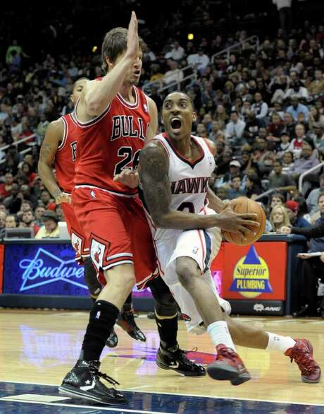 Atlanta Hawks guard Jeff Teague, right, tries to get by the defense of Chicago Bulls' Kyle Korvar during the first half of an NBA basketball game on Saturday, Jan. 7,  2012, in Atlanta. Photo: AP