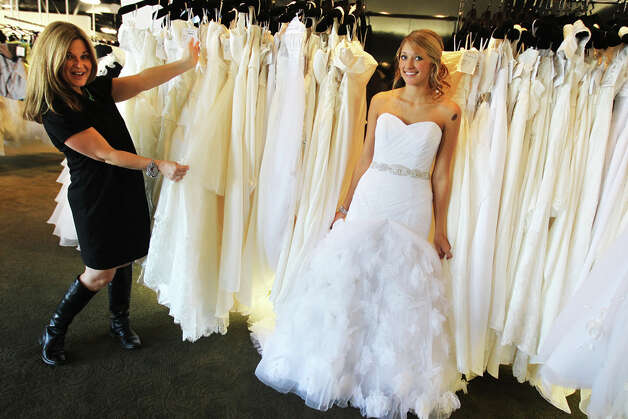 Giselle Drake a stylist at Impression Bridal models a gown as stylist and