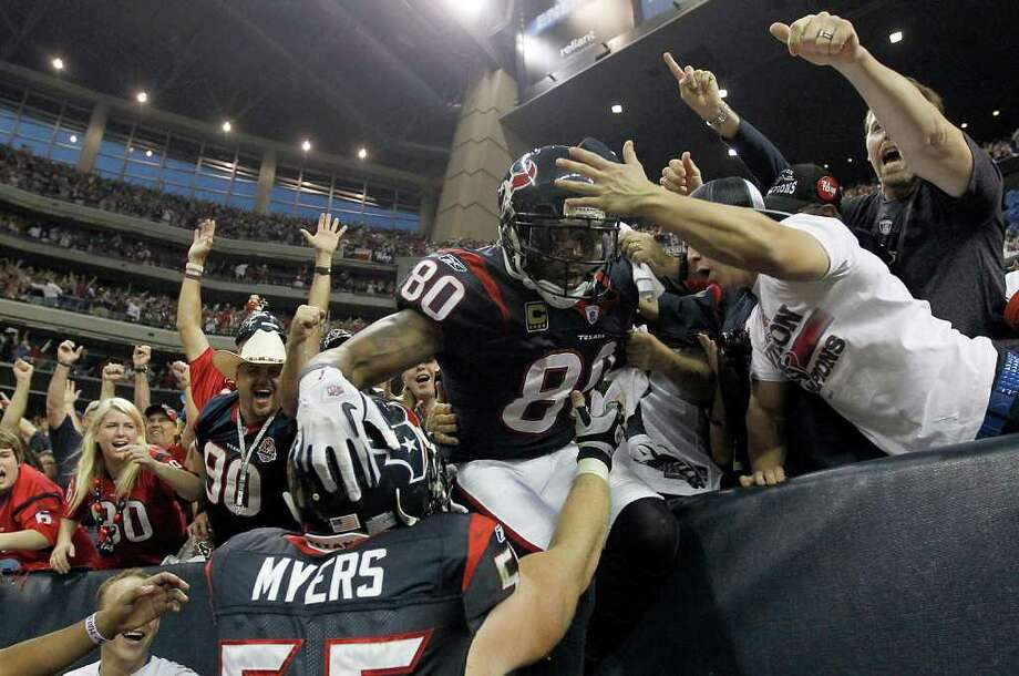 Texans receiver Andre Johnson, who waited nine long years before getting into his first playoff game, celebrated his third-quarter touchdown that gave the team a 24-10 lead with teammate Chris Myers and fans on Saturday. Photo: Karen Warren / © 2012  Houston Chronicle