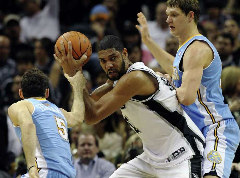 Spurs' Tim Duncan (center) battles against Denver Nuggets' Timofey Mozgov (right) and Rudy Fernandez (05) in the second half at the AT&T Center on Saturday, Jan. 7, 2012. Spurs won 121-117. Kin Man Hui/kmhui@express-news.net Photo: KIN MAN HUI, ~ / SAN ANTONIO EXPRESS-NEWS