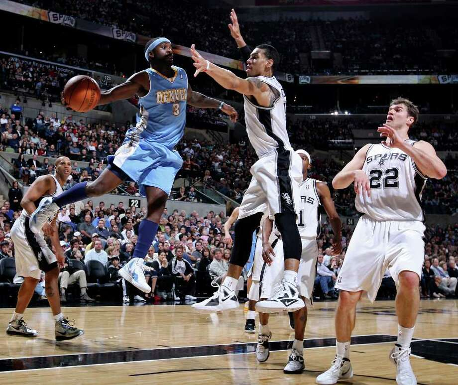 FOR SPORTS - Denver Nuggets' Ty Lawson looks to pass around San Antonio Spurs' Danny Green during first half action Saturday Jan. 7, 2012 at the AT&T Center. Photo: EDWARD A. ORNELAS / SAN ANTONIO EXPRESS-NEWS (NFS)