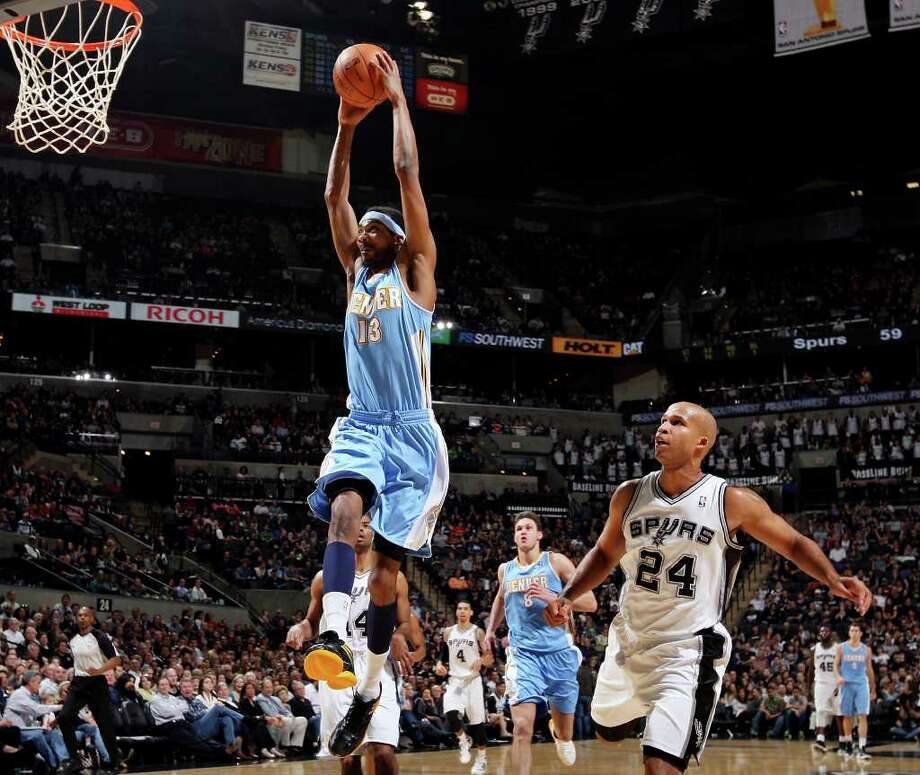 FOR SPORTS - Denver Nuggets' Corey Brewer goes up for a dunk ahead of San Antonio Spurs' Richard Jefferson during first half action Saturday Jan. 7, 2012 at the AT&T Center. Photo: EDWARD A. ORNELAS / SAN ANTONIO EXPRESS-NEWS (NFS)