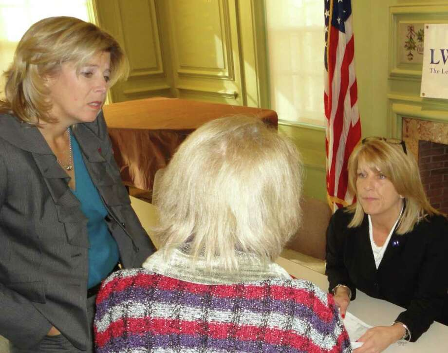State Reps. Kim Fawcett, left, and Brenda Kupchick, right, talk with a constituent at a legislative forum sponsored Saturday by the Fairfield League of Women Voters in the Fairfield Public Library. Photo: Meg Barone