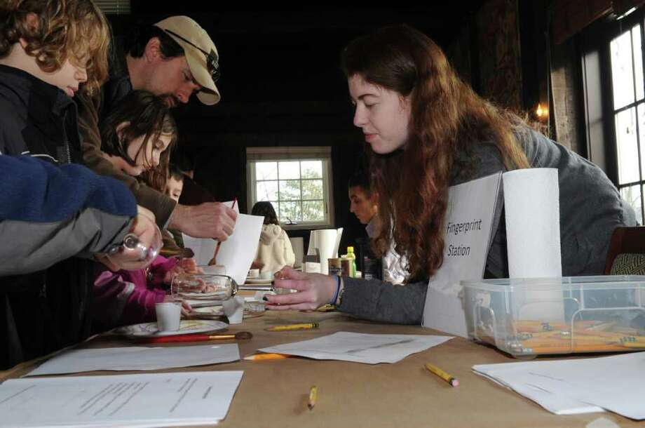 "From left, Aidan Munoz, 10, Evie Girard, 8, father Chris, and brother Harrison, 6, watch while teacher Klara Zimmerman, 18, demonstraits how to fingerprint during the Greenwich Historical Society's Junior Detective Day Sunday, Jan 8, 2012.  In the program, a valuable letter from the ""Everyday Heroes"" exhibition at the society has been stolen and replaced by a forgery.  Children visit the ""scene of the crime"" and employ techniques used by real police to solve the mystery. Photo: Helen Neafsey / Greenwich Time"