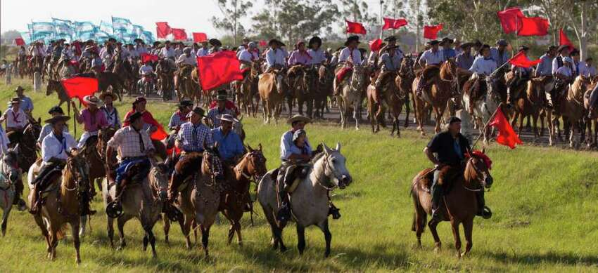 Men ride their horse towards the sanctuary of the legendary figure 'Gauchito Gil,' to mark the anniversary of death, near Mercedes, in Argentina's Corrientes state, Sunday Jan. 8, 2012.