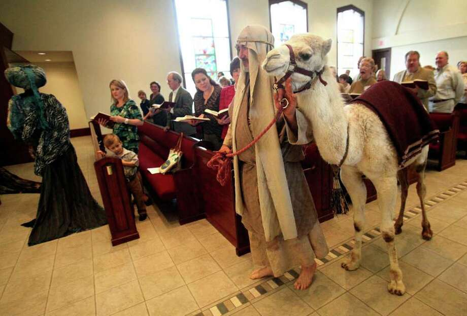 "The Magi lead Mike Smilie and ""Carrie"" the camel down the center aisle in the sanctuary at St. Francis Episcopal Church on Sunday, Jan. 8, 2012, in Houston.  The Epiphany is a Christian holiday celebrating the visit of the Magi, the three wise men and also called kings, to the infant Jesus in Bethlehem. Photo: Mayra Beltran, Houston Chronicle / © 2011 Houston Chronicle"