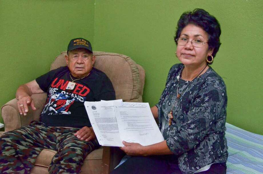 Erminia Molina, the daughter and care taker of World War II veteran jesus C. Garcia who is seated in the background, holds some of the documents she and her attorneys have filed in an effort to get answers about her father's VA benefits have been manager for the last 15 years when a lawyer from San Antonio was named as his fiduciary in 1995. Photo: RICARDO SANTOS / LAREDO MORNING TIMES