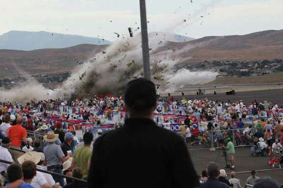 FILE - In this Sept. 16, 2011, file photo veteran Hollywood stunt pilot Jimmy Leeward's souped-up World War II-era fighter plane, P-51 Mustang, crashes into the edge of the grandstands, sending shrapnel into the crowd, at the Reno Air Show in Reno Nevada. Eleven people died and about 70 more were badly injured. That some victims would still support such events and return to them underscores the powerful fascination of air shows and races Tuesday, Jan. 10, 2012, the National Transportation Safety Board in Washington will hold a hearing to address and answer questions about safety and acceptable risk. (AP Photo/Ward Howes, File)