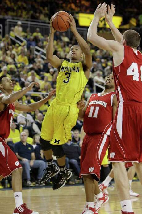 Michigan guard Trey Burke, who finished with 14 points, goes up for a shot against Wisconsin's Jordan Taylor (11) and Frank Kaminsky. Photo: AP
