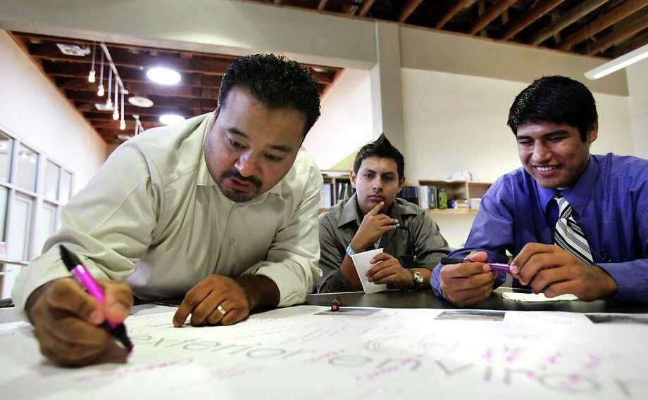 Fernando Flores, left, an architect with OCO Architects, writes notes during a meeting with The Highlands High School Engineering, Architecture and Construction Team, including Eleazar Robles, center, and Leonardo Rocha, right. The students met with architects from Pfluger and OCO Architects, to give ideas for the bond funded renovation of the high school.  Wednesday, Nov. 30, 2011. Photo Bob Owen/rowen@express-news.net Photo: BOB OWEN, SAN ANTONIO EXPRESS-NEWS / rowen@express-news.net