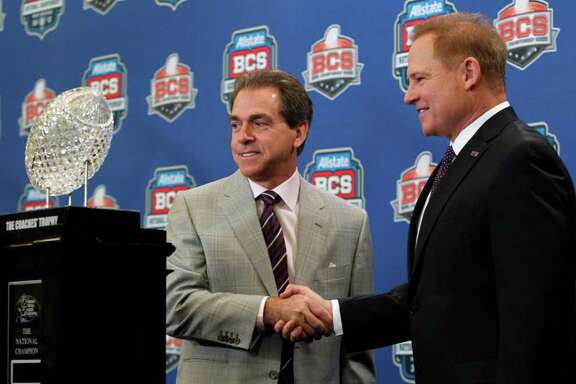 LSU head coach Les Miles, right, shakes hands with Alabama head coach Nick Saban during a news conferemce for the BCS National Championship college football game Sunday, Jan. 8, 2012, in New Orleans. (AP Photo/Dave Martin)
