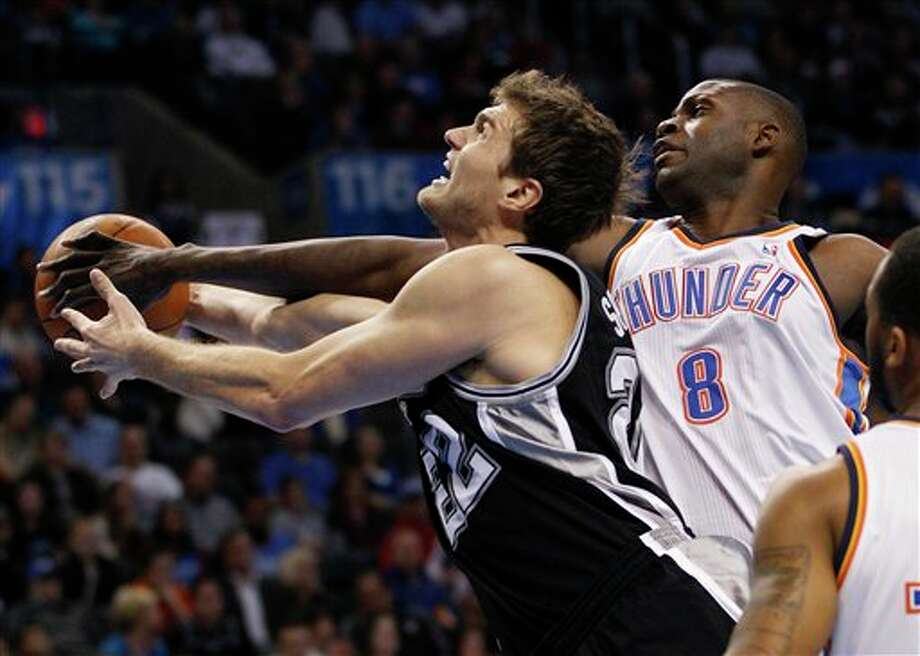 Oklahoma City Thunder center Nazr Mohammed (8) knocks the ball away from San Antonio Spurs forward Tiago Splitter (22) in the first quarter of an NBA basketball game in Oklahoma City, Sunday, Jan. 8, 2012. (AP Photo/Sue Ogrocki) Photo: Sue Ogrocki, Associated Press / AP