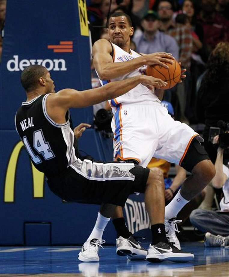 Oklahoma City Thunder guard Thabo Sefolosha, right, of Switzerland, knocks over San Antonio Spurs guard Gary Neal (14) as he drives to the basket in the first quarter of an NBA basketball game in Oklahoma City, Sunday, Jan. 8, 2012. (AP Photo/Sue Ogrocki) Photo: Sue Ogrocki, Associated Press / AP