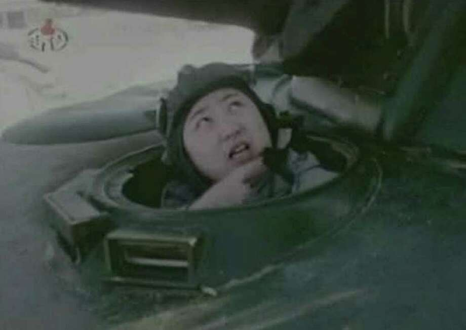"""In this undated image made from KRT video, North Korea's new young leader Kim Jong Un appears from a military vehicle at an undisclosed place in North Korea, aired Sunday, Jan. 8, 2012. Kim Jong Un, who was named """"supreme leader"""" of North Korea's people, ruling Workers' Party and military following the death last month of his father, Kim Jong Il, was shown observing firing exercises and posing for photographs with soldiers in footage that was shot before his father's death and aired as a documentary Sunday. (AP Photo/KRT via APTN) TV OUT, NORTH KOREA OUT"""