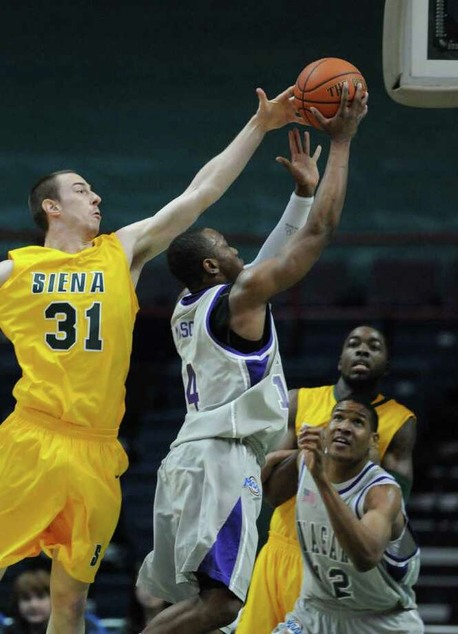 Owen Wignot of Siena, left, goes up to block the shot of Antoine Mason of Niagara during their game at the Times Union Center on Sunday, Jan. 8, 2012 in Albany.   (Paul Buckowski / Times Union) Photo: Paul Buckowski