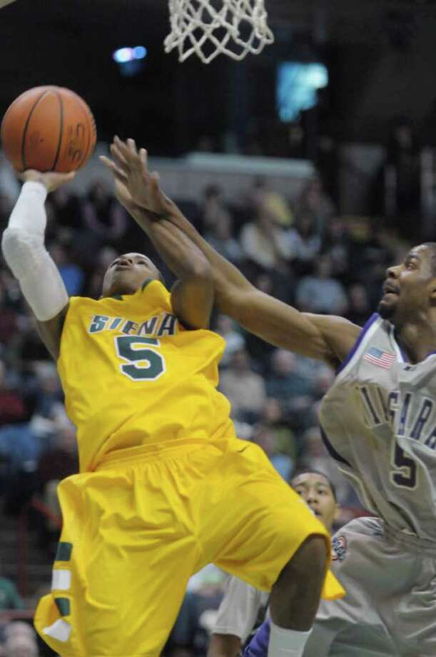 Evan Hymes of Siena, left, puts up a shot over a  Niagara player during their game at the Times Union Center on Sunday, Jan. 8, 2012 in Albany.   (Paul Buckowski / Times Union) Photo: Paul Buckowski