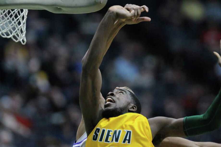 OD Anosike of Siena has his fingers bent back by a Niagara defender after Anosike scored a basket during their game at the Times Union Center on Sunday, Jan. 8, 2012 in Albany.   (Paul Buckowski / Times Union) Photo: Paul Buckowski